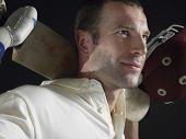 pic of cricket bat  - Closeup of a cricket player holding cricket bat behind shoulders against black background - JPG