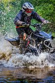 Quad Rider Through Water Stream