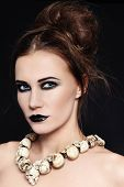 stock photo of freaky  - Portrait of young beautiful woman with black lipstick and gothic skull necklace - JPG