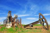 stock photo of oil rig  - abandoned oil pump jack in field summer day - JPG
