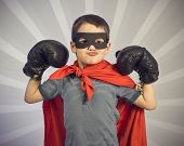 picture of superhero  - Superhero kid wearing boxing gloves on a gray background - JPG