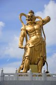 stock photo of gatekeeper  - A giant statue of a guardian guarding the entrance to a Chinese temple in Malaysia - JPG