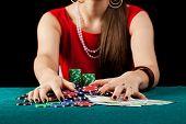 stock photo of gambler  - An elegant female gambler taking chips and banknotes - JPG