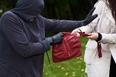 stock photo of snatch  - Agressive thief in the park snatching a purse - JPG