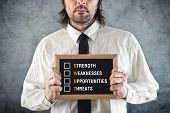 foto of swot analysis  - Businessman holding blackboard with SWOT ANALYSIS title - JPG