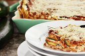 image of lasagna  - A serving of zucchini lasagna with fresh zucchini and casserole dish in background - JPG