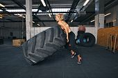 picture of physical exercise  - Fit female athlete flipping a huge tire - JPG