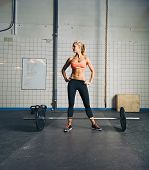 pic of barbell  - Fit young woman standing at gym with barbell on floor - JPG