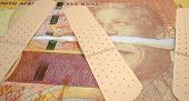 stock photo of nelson mandela  - A concept picture of a regular South African two hundred rand note torn in two length ways and held together by medical plasters on an isolated background - JPG