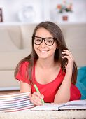 image of belly-band  - Portrait of a teenage girl taught lessons sitting on the floor at home - JPG