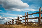 image of log fence  - wooden rustic fence in village and blue sky with clouds - JPG