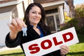 stock photo of real-estate agent  - Happy Attractive Hispanic Woman Holding Keys and Sold Sign In Front of House - JPG