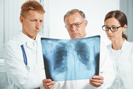 pic of pneumonia  - Older man doctor and young doctors examine x - JPG