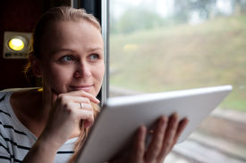 stock photo of thoughtfulness  - Smiling young woman traveling by train holding a tablet in her hands as she stares thoughtfully into the air through the window with her hand to her chin - JPG