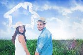foto of shoulder-blade  - Happy hipster couple holding hands and smiling at camera against field of grass under blue sky - JPG