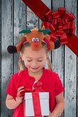stock photo of rudolph  - Cute little girl wearing rudolph headband against wood with festive bow - JPG