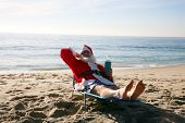 picture of christmas claus  - Santa Claus relaxing in his lounge chair on a tropical sandy beach  - JPG