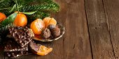 foto of tangerine-tree  - Chocolate truffles and tangerines with fir tree branches on a wooden table - JPG