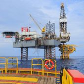 foto of drilling platform  - Offshore Jack Up Drilling Rig Over The Production Platform in The Middle of The Sea  - JPG