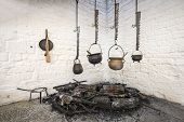stock photo of paint pot  - Old midieval rustic metal kitchen pots hanging over a fire - JPG
