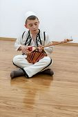 picture of string instrument  - young boy playing traditional string instrument on wooden floor - JPG
