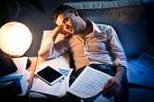 pic of nervous breakdown  - Tired businessman sleeping on sofa at home surrounded by paperwork - JPG