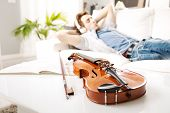 foto of violin  - Violin close-up with man relaxing and listening to music on background. ** Note: Shallow depth of field - JPG