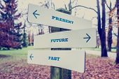picture of past future  - Conceptual Design of Present Future and Past on Direction Sign Board on a Grassy Landscape with Trees at the Background - JPG