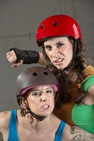 image of roller-derby  - Two tough female roller derby skaters with clenched teeth - JPG
