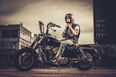 pic of ape-man  - Tattooed biker and his bobber style motorcycle on a city streets  - JPG