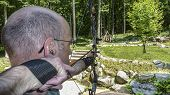 picture of bow arrow  - Bow and Arrow hunter practicing on a target in the backyard using a compound bow and a quick release trigger - JPG