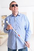 pic of blind man  - Blind man with white stick and dark glasses at home - JPG