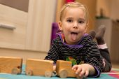 picture of cheeky  - Cheeky blond girl is playing with a wooden toy - JPG