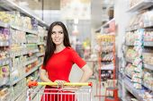 stock photo of local shop  - Portrait of a young girl in a market store with a shopping cart - JPG