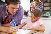 stock photo of 11 year old  - Father Helping Daughter To Draw Picture At Kitchen Table - JPG