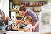 picture of father daughter  - Daughter Helping Father To Cook Meal In Kitchen - JPG