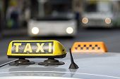 stock photo of headlight  - automobile emblem and sign of a taxi against city streets with the vague image of buses and the included headlights - JPG