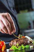 picture of porterhouse steak  - Chef in hotel or restaurant kitchen cooking - JPG