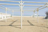 image of gazebo  - A white gazebo and cabins on the beach of Rimini in Italy during a sunny day - JPG