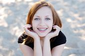 stock photo of braces  - Pretty girl wearing braces smiling cheerfully sitting outdoors - JPG