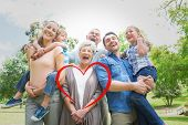 stock photo of extended family  - Portrait of cheerful extended family at park against heart - JPG