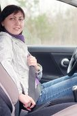 pic of seatbelt  - Woman putting on a seatbelt for safety  - JPG