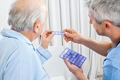 picture of male nurses  - Male caretaker showing prescription medicine to senior man in bedroom at nursing home - JPG