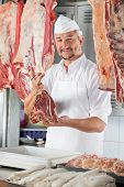 stock photo of slaughterhouse  - Portrait of confident male butcher holding raw meat at counter in shop - JPG