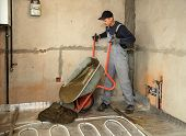picture of wheelbarrow  - Man carries a wheelbarrow with concrete to fill the floor - JPG