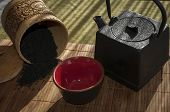 foto of black tea  - on bamboo Mat cast iron kettle and a Cup of hot tea spilled black tea