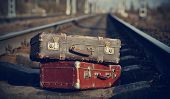 stock photo of old suitcase  - The image of two old vintage suitcases forgotten on railway tracks - JPG
