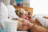stock photo of sleep  - Daughter Plays With Mobile Phone In Bed As Parents Sleep - JPG