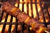 image of bbq party  - Beef Kebabs On The Hot BBQ Grill Closeup. Flaming Charcoal Grill In The Background. Cookout Snack For Summer Spring Weekend Barbeque or Picnic Party.