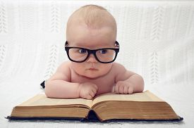 pic of child development  - funny portrait of adorable little baby in glasses with old book  - JPG